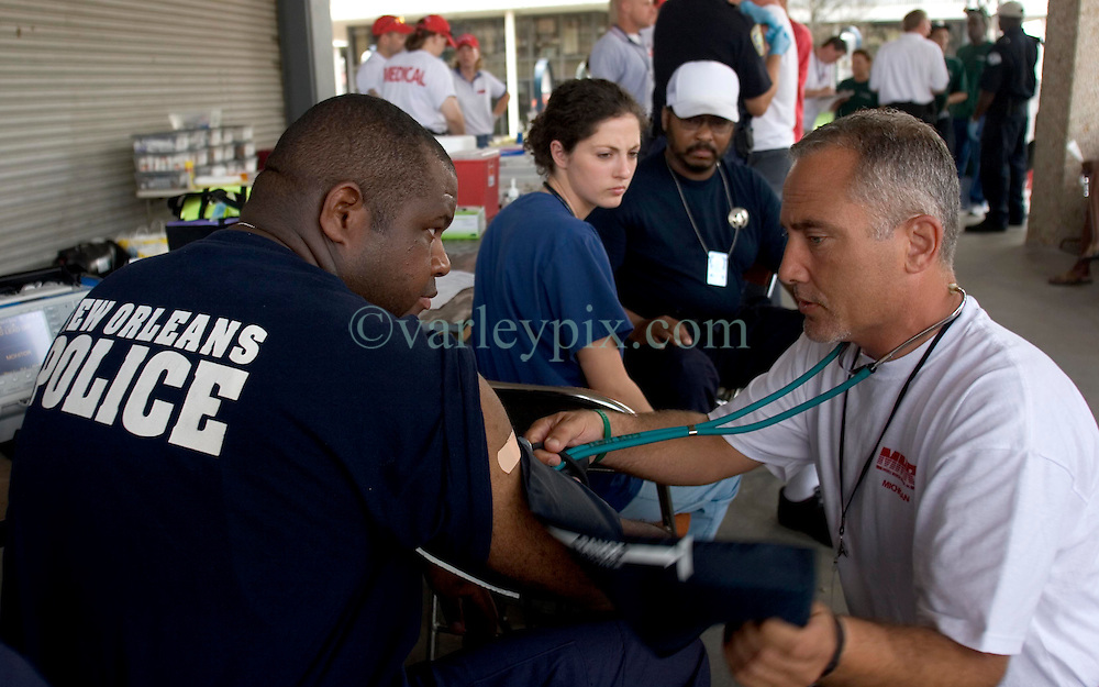 10 Sept 2005. New Orleans, Louisiana.  Hurricane Katrina aftermath.<br /> NOPD officer Taj Magee of the 7th district who fell into the fetid flood waters has his health monitored by Dr David Taylor of the Mobile Medical Response team at the bottom of Canal Street. Officer Magee complained of multiple serious symptoms after his immersion in the water.<br /> Photo; &copy;Charlie Varley/varleypix.com