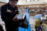 Postman Yoshinori Shoji removes postal items from his bag of residents left homeless by the March 11 quake and tsunami at the KadonowakiJunior HighSchool in Ishinomaki, Miyagi Prefecture, Japan on Tuesday 24 May 2011. Post office branches and delivery centresaremaking sure thatmail gets through to the 1,112 temporary shelters across the north-east of Japan, with post that cannot be delivered being returned to senders..Photographer: Robert Gilhooly