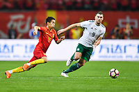 Wei Shihao, left, of Chinese national men's football team kicks the ball to make a pass against Sam Vokes of Wales national football team in the semi-final match during the 2018 Gree China Cup International Football Championship in Nanning city, south China's Guangxi Zhuang Autonomous Region, 22 March 2018.