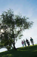 Silhouettes of group of golfers walking on golf course
