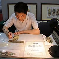 Asia, China, Kunming. Chinese rrtist paints on leaf.