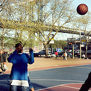 Youths play basketball on a recreational court in the late afternoon sunlight, Manhattan, New York, USA. 23rd July 2011. Photo Tim Clayton