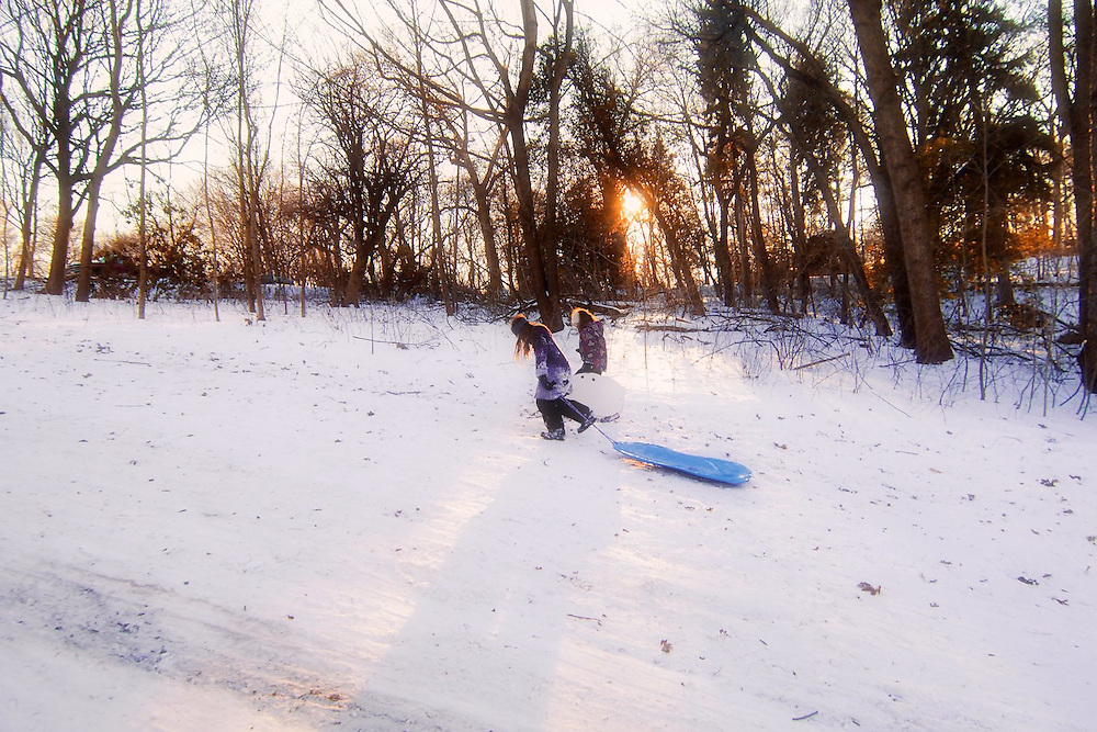 Thomas Mansion Sledding hill, Philadelphia PA USA - December 12th 2010; <br /> <br /> Two girls drag their sleds up the hill.<br /> <br /> Not a paticular beautiful image with all the debry laying around and the muddy colors but it is the moment that caught me; two girls dragging sleds (and themselfs) up a hil at the end of an exciting day in the snow<br /> <br /> Creatively processed, edited, toned & apped file as alternative to original image