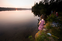A girl fishing as the sun sets over Otter Lake in Greenfield State Park in Greenfield, New Hampshire.
