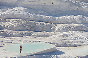 One tourist in one of the pools at Pamukkale. The hard, white mineral deposits, which from a distance resemble snow, are caused by the high mineral content of the natural spring water which runs down the cliff and congregates in warm pools on the terraces. This is such a popular tourist attraction that strict rules had to be established in order to preserve its beauty, which include the fact that visitors may no longer walk on the terraces. Those who want to enjoy the thermal waters, however, can take a dip in the nearby pool, littered with fragments of marble pillars.