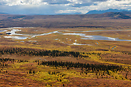 The Maclaren River winds its way through the tundra valley and the Alaska Range of Interior Alaska. Autumn. Afternoon.