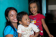 Jula Eha  at home with her children. <br /> <br /> Jula runs a small shop from the front of her house in a quiet residential area near the town of Bogor, Indonesia.<br /> <br /> Her shop had mixed success at first and she used to become demotivated, but after subscribing to Usaha Wanita she regained her motivation and started to think of more creative ways to make her business a success. <br /> <br /> As a result her profits have increased and she is now saving money in an education fund for her children. <br /> <br /> She has also been able to follow Usaha Wanita's advice on savings and investments and she has joined a savings scheme and purchases new fridges and display cabinets for her store.