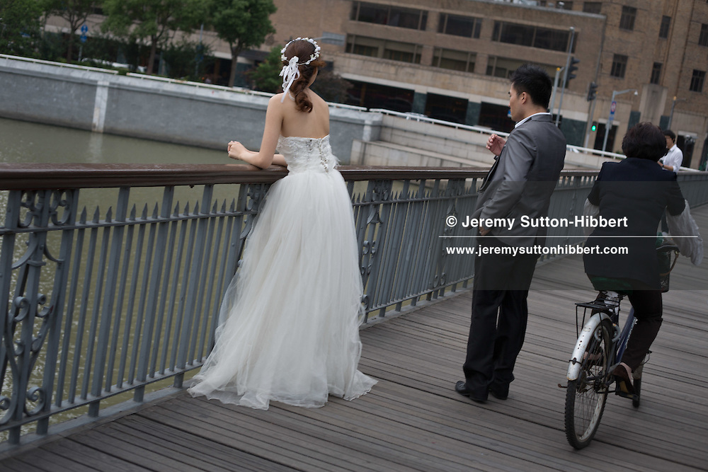 Wedding photos and bride, bridesmaid, on Waibaidu Bridge steel bridge near the Bund, in Shanghai, China, Monday 4th June 2012.