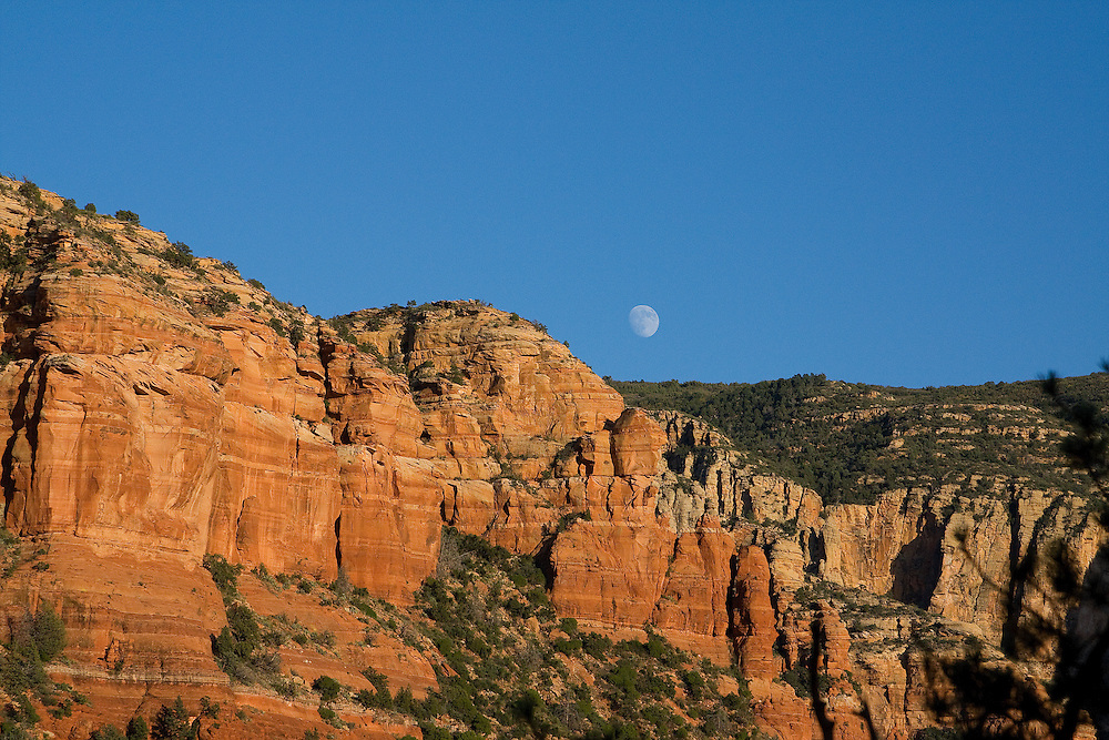 The moon rises over red rocks in Sedona, Arizona.