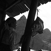 An ethnic minority girl looks out past a dangling pig's head at an early morning market in Ha Giang, Vietnam's northernmost province, 22 June, 2007. As cities like Hanoi and Ho Chi Minh roar with Vietnam's economic boom, Ha Giang remains a quiet, serene and beautiful mountain backwater along the Chinese border.