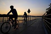 Bikers ride down the Four Rivers bike trail at sunset in Daegu, South Korea.