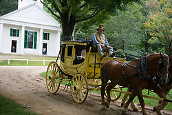 A yellow horse drawn carriage passes along a dirt road - Old Sturbridge Village (OSV), a re-created New England town of the 1830s, is a living history museum in Sturbridge, Massachusetts.  OSV, the largest living museum in New England, stands on 200 acres on farm land that once belonged to David Wight.