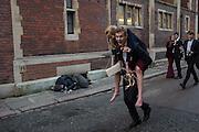 Leaving the Clare May Ball on piggyback, Homeless man sleeping, Cambridge College May Balls. Cambridge, England. 14 June 2016