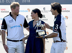 Nacho Figures presents the trophy with Meghan, Duchess of Sussex, wearing a navy blue dress by Carolina Herrera, and Prince Harry, Duke of Sussex following the Sentebale ISPS Handa Polo at the Royal County of Berkshire Polo Club on July 26, 2018.