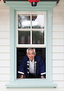 Takemi Takahashi, manager of Korakukan, looks out from one of the British-style windows that grace the exterior of the playhouse in Kosaka, Akita Prefecture Japan on 10 Aug. 2015. Made entirely from wood, the theater was opened in 1910 and was registered as an Important Cultural Property in 2007. Photographer: Rob Gilhooly