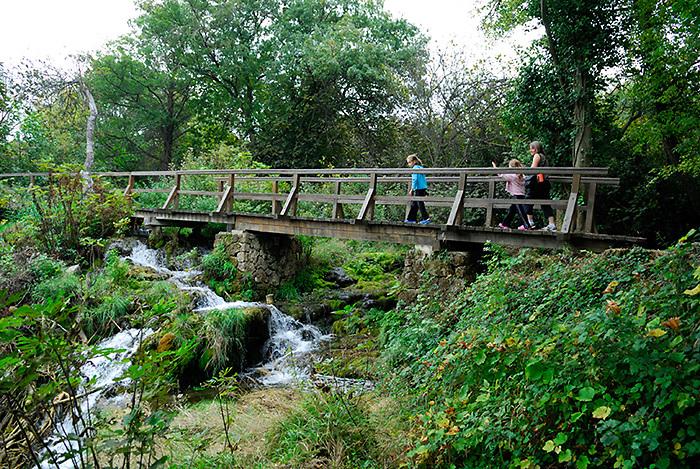 Woman and two girls on bridge and walkway over waterfall, Krka National Park, Croatia