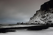 Snow on Vik Beach in southern Iceland, just after sunrise on an overcast day.
