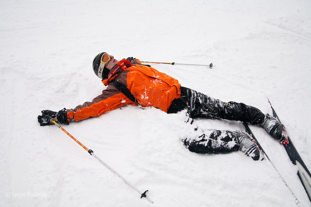 A skier takes a breather after falling down in the snow in Colorado.