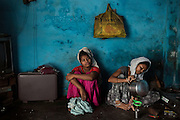 After having washed her hair, Poonam, 13, (left) is waiting for chai tea to be served by her oldest sister Arti, 19, while sitting on the floor of their newly built home in Oriya Basti, one of the water-contaminated colonies in Bhopal, Madhya Pradesh, India, near the abandoned Union Carbide (now DOW Chemical) industrial complex.