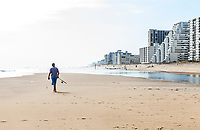 Ocean City beach with a man in the foreground walking towards the surf with his fishing pole, Ocean City, Maryland, USA.