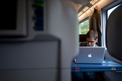 Businessman working on laptop in first class carriage on German ICE high speed express train