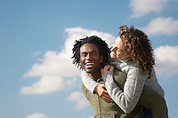 Man giving woman piggyback against sky