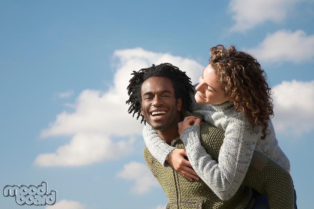 Man giving woman piggyback against sky