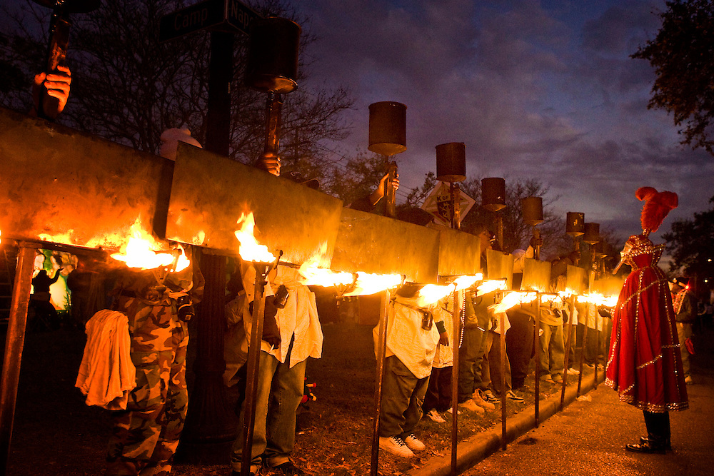 One of the oldest traditions of Mardi Gras, Flambeaux carrying kerosene torches line up for final inspection before parading during Mardi Gras in the Uptown area of New Orleans, Louisiana, USA.