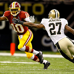 September 9, 2012; New Orleans, LA, USA; Washington Redskins quarterback Robert Griffin III (10) runs away from New Orleans Saints safety Malcolm Jenkins (27) during the first half of a game at the Mercedes-Benz Superdome. Mandatory Credit: Derick E. Hingle-US PRESSWIRE