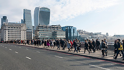 © Licensed to London News Pictures. 05/04/2016. London, UK. City of London office commuters en route to work, cross London Bridge on the last day of the 2015/16 tax year, the last day when UK individuals can make contributions to tax efficient investments such as ISAs, many of which investments are managed in the City of London. Photo credit : Stephen Chung/LNP