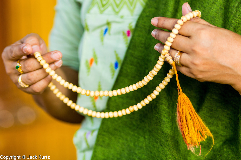 15 JUNE 2013 - YANGON, MYANMAR: A woman prays with prayer beads at Shwedagon Pagoda. The Shwedagon Pagoda is officially known as Shwedagon Zedi Daw and is also called the Great Dagon Pagoda or the Golden Pagoda. It is a 99 metres (325ft) tall pagoda and stupa located in Yangon, Burma. The pagoda lies to the west of on Singuttara Hill, and dominates the skyline of the city. It is the most sacred Buddhist pagoda in Myanmar and contains relics of the past four Buddhas enshrined: the staff of Kakusandha, the water filter of Koṇāgamana, a piece of the robe of Kassapa and eight strands of hair fromGautama, the historical Buddha. The pagoda was built between the 6th and 10th centuries by the Mon people, who used to dominate the area around what is now Yangon (Rangoon). The pagoda has been renovated numerous times through the centuries. Millions of Burmese and tens of thousands of tourists visit the pagoda every year, which is the most visited site in Yangon.  PHOTO BY JACK KURTZ