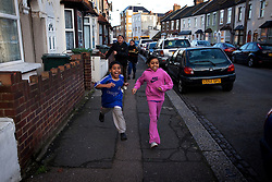 Bibi's children play outsides their home. They live in a small house in East London. It is cold and damp and they have breathing problems, her older son suffers from incontinence and the room the children all share smells constantly. London, UK.