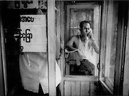Man pays to talk in a private telephone box, as mobile telephones have been made by government regulations far beyond the means of average Burmese, Yangon, Burma.