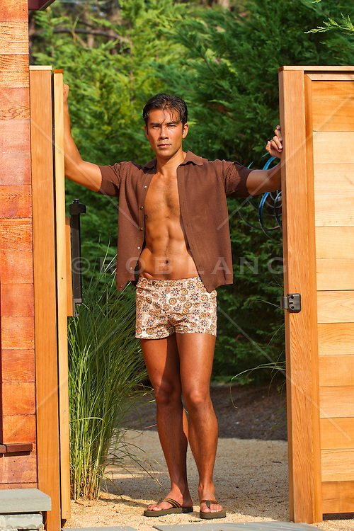 man standing in a backyard entrance wearing a bathing suit and open shirt