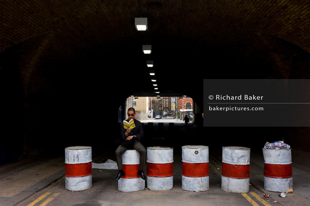 Man reads a book while sitting on old concrete-filled oil drums at entrance to east London tunnel.