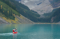 Canoeists paddling red canoes on Lake Louise, Banff National Park