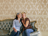 Two young women sitting on sofa portrait
