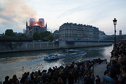 Bystanders look on as flames and smoke are seen billowing from the roof at Notre-Dame Cathedral with the Seine and boats river in Paris on April 15, 2019. A fire broke out at the landmark Notre-Dame Cathedral in central Paris, potentially involving renovation works being carried out at the site, the fire service said.Images posted on social media showed flames and huge clouds of smoke billowing above the roof of the gothic cathedral, the most visited historic monument in Europe. Photo by Raphael Lafargue/ABACAPRESS.COM
