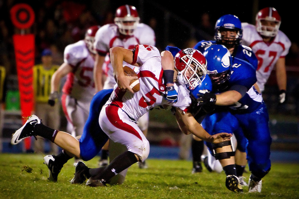 Sandpoint High's quarterback Brandon Hawkins is drug down from behind by a Coeur d'Alene High defender during the first half of Friday's game.