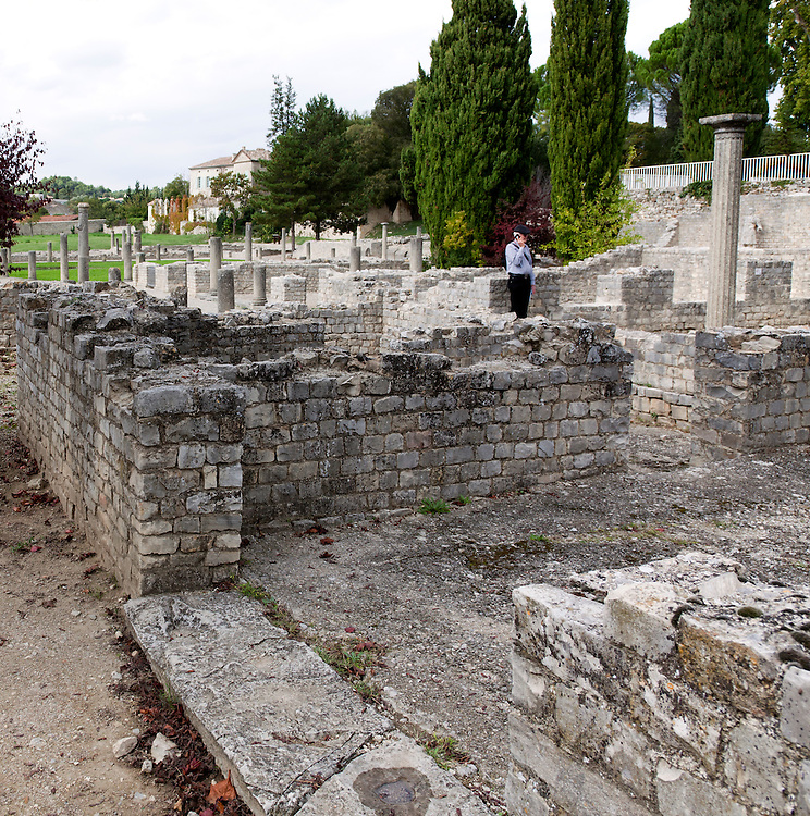 A tourist listens to an audioguide as he explores the Roman ruins of La Villasse (Vasio in 1st century BC), surviving well today in the bustling heart of Vaison-la-Romaine, Ventoux, Provence, France.