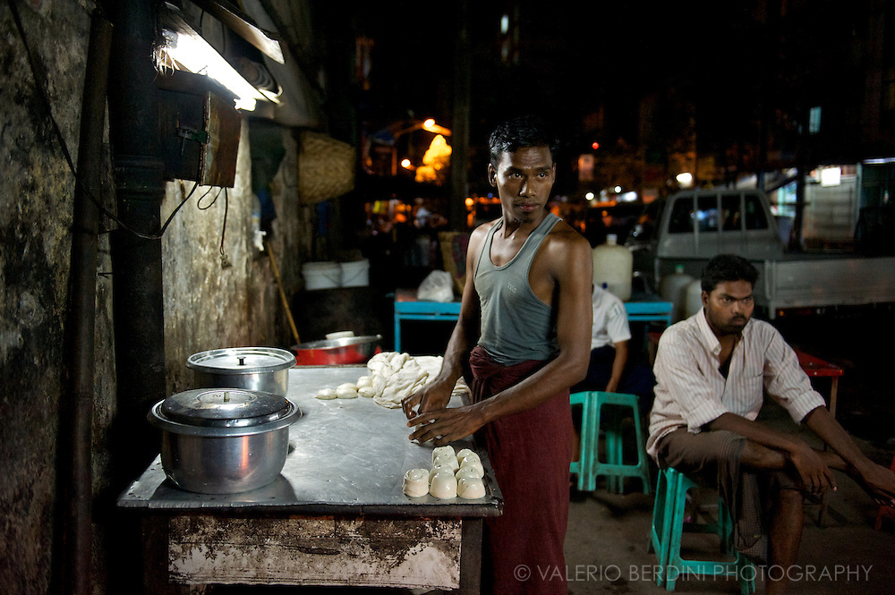 A man prepares doughs to be fried in one of the many lively food stalls of Rangoon nights.