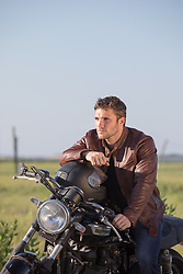 handsome man sitting on a motorcycle in rural America