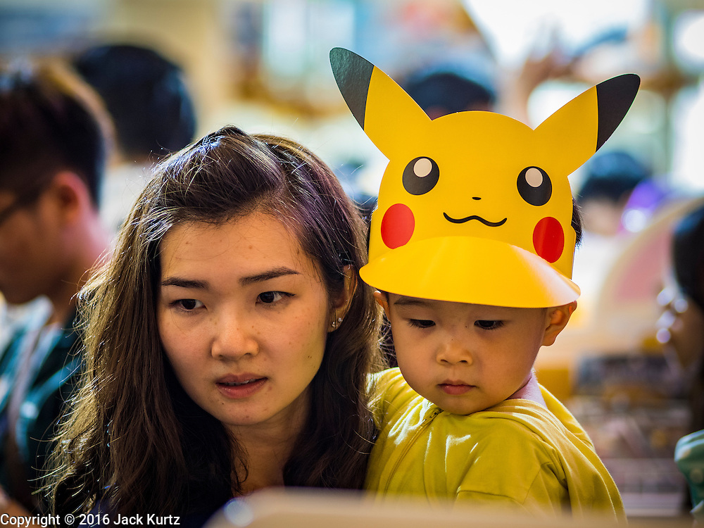 08 JANUARY 2016 - BANGKOK, THAILAND:  A woman and her son shop for Pokémon toys during Children's Day festivities at Paragon Mall, a high end mall in Bangkok. National Children's Day falls on the second Saturday of the year. Thai government agencies sponsor child friendly events, malls throw parties and special shopping events for children and the military usually opens army bases to children, who come to play on tanks and artillery pieces.    PHOTO BY JACK KURTZ