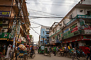 Bustling and busy street scene in Cox Bazar, Chittagong Division, Bangladesh, Asia.  Cox Bazar is a busy city, fishing port and tourism centre and district headquarters in southeastern Bangladesh.  Electricity wires hang between commercial buildings across the busy road with rikshaws parked and moving.   (photo by Andrew Aitchison / In pictures via Getty Images)