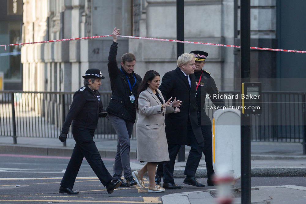 The morning after the terrorist attack at Fishmongers Hall on London Bridge, in which Usman Khan (a convicted, freed terrorist) killed 2 during a knife a attack, then subsequently tackled by passers-by and shot by armed police - Met Police Commissioner Cressida Dick; Home Secretary Priti Patel; Prime  Minister Boris Johnson, and City of London Commissioner Ian Dyson leave the cordon after viewing the crime scene, on 30th November 2019, in London, England.