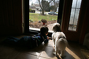 Victor Padilla, 3, and the family dog, Romeo, watch Victor's speech therapists leave the Padilla home in Rochester, New York on Monday, March 6, 2017. Victor has CLOVES Syndrome, a rare overgrowth syndrome diagnosed in only 200 people worldwide.