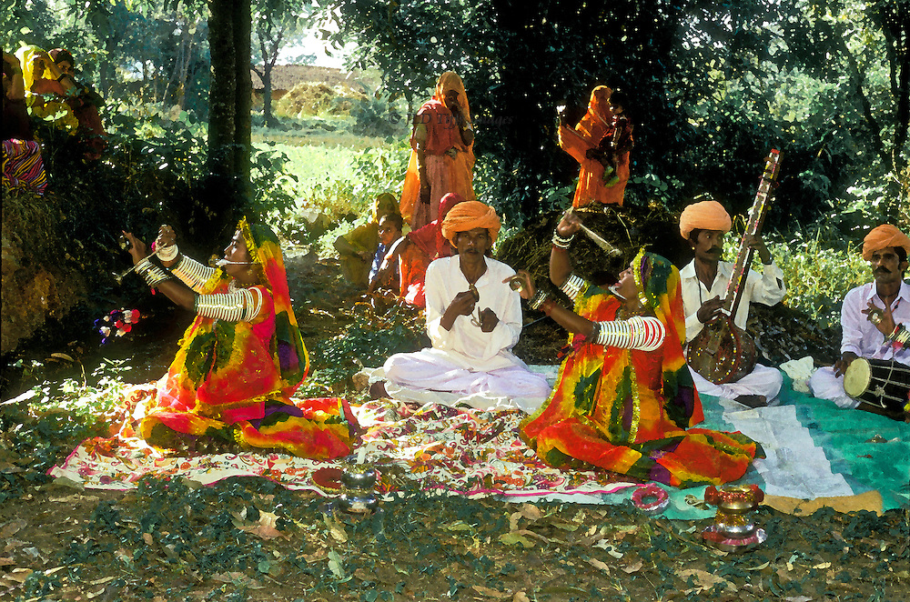 Members of the Rajasthani Kamar tribe perform the Tera Tali which is an elaborate ritual with many elements of dance. It is generally performed by two or three women who sit on the ground. Manjiras, or small metal cymbals are tied to different parts of the body, mostly the legs, and with a cymbal in either hand the dancer strikes these in rhythm. The head is covered with a veil, and at times a small sword is clenched between the teeth and an ornamental pot balanced on the head.  This was a special performance for an Elderhostel tour group in a shady grove of mango trees north of Udaipur.
