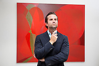 Young adult man thinking in front of painting in museum