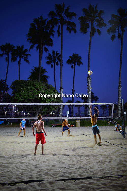 Group of young people playing night beach volleyball in Santa Monica beach, California.