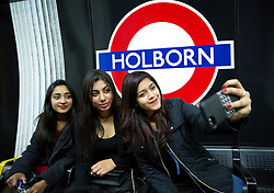© Licensed to London News Pictures. 16/12/2016. LONDON, UK.  Partygoers take a selfie while waiting for the Picadilly line at Holborn tube station, central London,  on Mad Friday. The Piccadilly Line is the latest route to begin a Night Tube service. Photo credit: ISABEL INFANTES/LNP